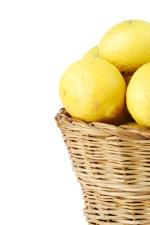Close-up of lemons in a wicker basket on white