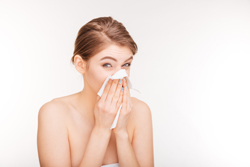 Unhappy young woman catched a cold and using paper handkerchief